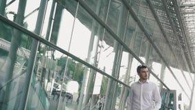 Homem de negócios seguro novo nos vidros e com a mala de viagem no fundo moderno da parede de vidro de terminal de aeroporto viaj video estoque