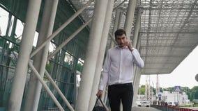 Homem de negócios seguro novo nos vidros e com a mala de viagem no fundo moderno do terminal de aeroporto Conceito de viagem do i filme