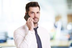 Homem de negócios seguro que faz uma chamada ao estar no escritório imagens de stock royalty free