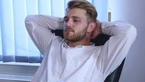 Homem de negócios seguro que relaxa em sua cadeira em seu escritório filme