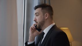 Homem de negócios seguro que tem o telefonema no hotel filme