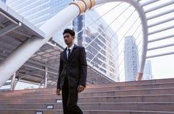 Homem de negócios seguro que vai para baixo e que anda em escadas Fotografia de Stock