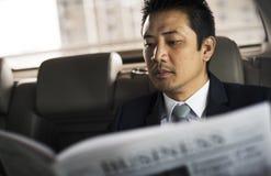 Homem de negócios Sit Read Newspaper Inside Car imagens de stock royalty free