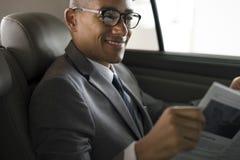 Homem de negócios Sit Read Newspaper Inside Car imagem de stock