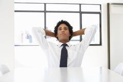 Homem de negócios Sitting At Desk no pensamento do escritório Foto de Stock Royalty Free