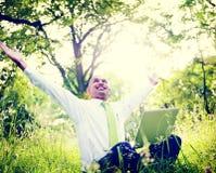 Homem de negócios Sitting In Forest With His Laptop Concept foto de stock