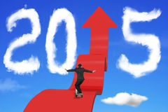 Homem de negócios Skateboarding no trajeto ascendente da seta com 2015 nuvens Fotos de Stock Royalty Free