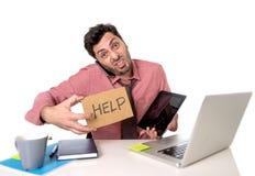 Homem de negócios sobrecarregado ocupado na mesa de escritório que trabalha no telefone celular do computador e na tabuleta digit Foto de Stock Royalty Free