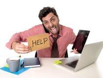 Homem de negócios sobrecarregado ocupado na mesa de escritório que trabalha no telefone celular do computador e na tabuleta digit Fotos de Stock Royalty Free