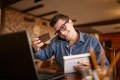 Homem de negócios sobrecarregado que fala no telefone celular que guarda o com o ombro, lendo escritas no caderno, comendo um bol fotos de stock royalty free