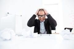 Homem de negócios sobrecarregado que trabalha no laptop e que tem a dor de cabeça foto de stock royalty free