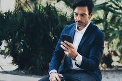 Homem de negócios de sorriso atrativo que faz a conversação video com os sócios pelo telefone celular Homem que usa o smartphone  fotos de stock