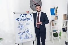 homem de negócios de sorriso que aponta no whiteboard com gráficos obtidos da inscrição e de negócio da motivação foto de stock royalty free