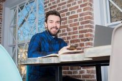 Homem de negócios de sorriso que guarda o telefone celular durante o trabalho no laptop no escritório foto de stock royalty free