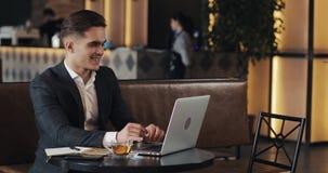 Homem de negócios de sorriso que usa o laptop que senta-se na tabela do café filme