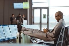 homem de negócios de sorriso que usa o smartphone ao esperar o voo fotos de stock royalty free