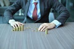 Homem de negócios Stacking Coins na ordem crescente na mesa foto de stock