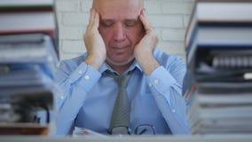 Homem de negócios Suffering uma dor de cabeça grande na sala do escritório imagem de stock royalty free