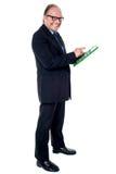 Homem de negócios superior alegre que usa uma calculadora imagens de stock royalty free