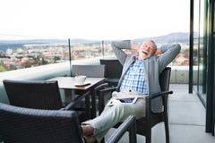 Homem de negócios superior com uma tabuleta no café do telhado Imagens de Stock Royalty Free