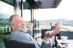 Homem de negócios superior com uma tabuleta no café do telhado Fotografia de Stock