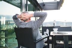 Homem de negócios superior com uma tabuleta no café do telhado Foto de Stock Royalty Free