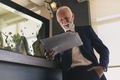 Homem de negócios superior que analisa a documentação foto de stock royalty free