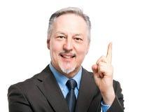 Homem de negócios superior que aponta seu dedo acima fotografia de stock royalty free