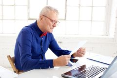 Homem de negócios superior que senta-se atrás de seu portátil e que faz algum documento no escritório fotos de stock