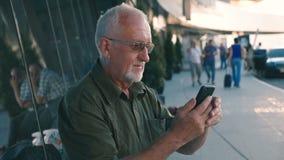 Homem de negócios superior que usa o ar livre do smartphone no terminal de aeroporto filme
