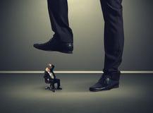 Homem de negócios superior sob o pé grande seu chefe Foto de Stock