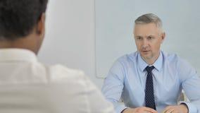 Homem de negócios superior Talking com o homem de negócios africano no escritório, entrevista video estoque