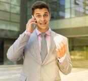 Homem de negócios surpreendido que fala no telefone fotografia de stock royalty free