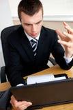 Homem de negócios surpreendido que olha seu portátil Foto de Stock