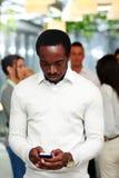 Homem de negócios surpreendido que usa o smartphone Imagem de Stock