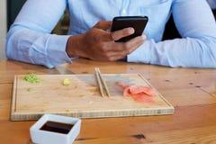 Homem de negócios terminado com o alimento que guarda o telefone celular Fotos de Stock