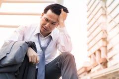 Homem de negócios triste com o terno que senta-se na maneira da caminhada da escada na cidade após a falha do projeto do negócio imagem de stock