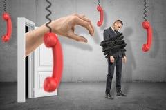 Homem de negócios triste, limite com fios, e mão enorme que emerge da entrada atrás de pronto para agarrá-lo com o telefone quatr foto de stock