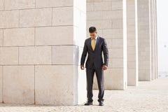 Homem de negócios triste que relaxa ao lado de alguma parede Fotografia de Stock Royalty Free