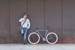Homem de negócios urbano à moda que está rua na chamada imagem de stock