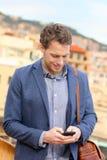 Homem de negócios urbano novo do telefone esperto no smartphone imagens de stock
