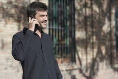 Homem de negócios urbano novo no telefone esperto na rua que fala em smar fotografia de stock