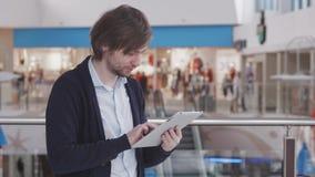 Homem de negócios Using Digital Tablet na sala de estar da partida do aeroporto Freelancer novo com a mala de viagem do laggage n Imagem de Stock