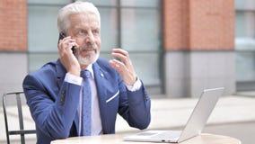 Homem de negócios velho irritado Talking no telefone filme