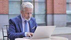 Homem de negócios velho irritado Working no portátil video estoque