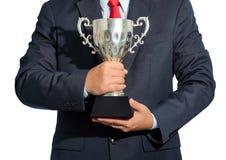 Homem de negócios, vencedor com o terno que guarda um troféu no backgrou branco Foto de Stock Royalty Free