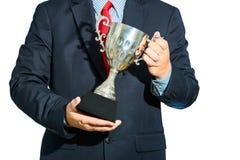 Homem de negócios, vencedor com o terno que guarda um troféu no backgrou branco Fotos de Stock