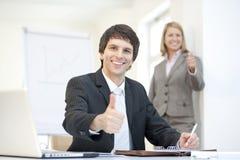 Homem de negócios vestido esperto com UO dos polegares, trabalhos de equipa Fotografia de Stock
