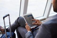 Homem de negócios Viewing Boarding Pass na sala de estar do aeroporto imagens de stock royalty free