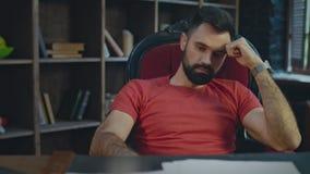 Homem de negócios virado que senta-se no escritório na noite Pensamento triste do homem de negócios video estoque